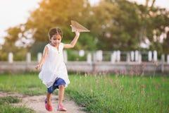 Gullig asiatisk barnflickaspring och spela det pappers- flygplanet för leksak Arkivfoton