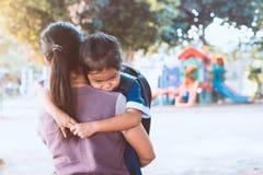 Gullig asiatisk elevflicka med ryggsäcken som kramar hennes moder fotografering för bildbyråer