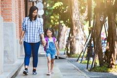 Gullig asiatisk elevflicka med ryggs?cken som rymmer hennes moderhand och g?r till skolan royaltyfria foton