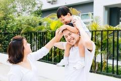 Gullig asiatisk fader som piggbacking hans son tillsammans med hans fru i parkera Upphetsad familj som spenderar tid samman med l royaltyfri bild