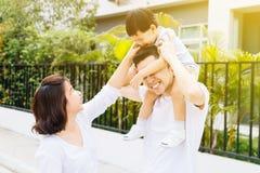 Gullig asiatisk fader som piggbacking hans son tillsammans med hans fru i parkera Upphetsad familj som spenderar tid samman med l arkivfoton