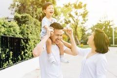 Gullig asiatisk fader som piggybacking hans son tillsammans med hans fru i parkera Upphetsad familj som spenderar tid samman med  royaltyfria foton