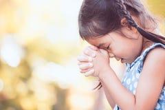 Gullig asiatisk flicka för litet barn som ber med vikt hennes hand arkivbild