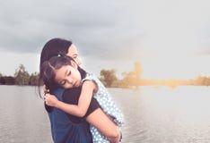 Gullig asiatisk flicka för litet barn som vilar på skuldra för moder` s royaltyfria bilder
