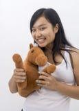 Gullig asiatisk flicka med en nallehäst Royaltyfri Fotografi