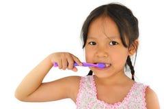 Gullig asiatisk flicka och tandborste Arkivfoton