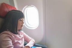 Gullig asiatisk flicka på flygplanet arkivbilder