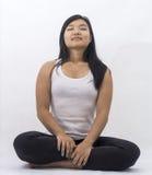 Gullig asiatisk flicka på isolerat meditera för bakgrund royaltyfri foto