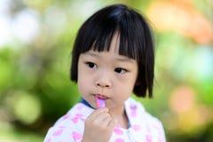Gullig asiatisk flicka som äter glass Arkivbilder