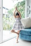Gullig asiatisk flicka som hemma gör yoga Royaltyfri Foto
