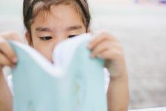 Gullig asiatisk flicka som läser en bok i skola Arkivfoton