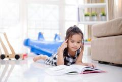 Gullig asiatisk flicka som läser en bok medan i det levande rummet Royaltyfria Foton