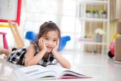 Gullig asiatisk flicka som läser en bok medan i det levande rummet Royaltyfria Bilder