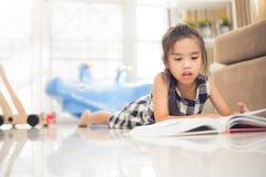 Gullig asiatisk flicka som läser en bok medan i det levande rummet Arkivfoto