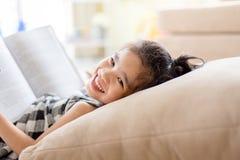 Gullig asiatisk flicka som läser en bok och ler tandvit medan i det levande rummet Royaltyfri Bild
