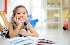 Gullig asiatisk flicka som läser en bok och ler tandvit medan i det levande rummet Arkivfoto