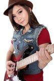 Gullig asiatisk flicka som spelar hennes gitarr, på vit bakgrund Arkivbild