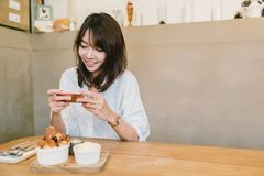 Gullig asiatisk flicka som tar fotoet av efterrätten på coffee shop Fritidsaktivitet eller mobiltelefonfotografi, matfotobegrepp royaltyfria bilder