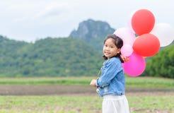 gullig asiatisk flickaleende- och innehavballong, arkivfoton