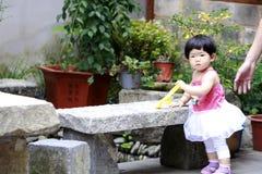 Gullig asiatisk kines behandla som ett barn flickalek med leksaken i en trädgård royaltyfri fotografi