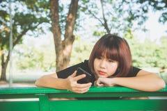 Gullig asiatisk kvinna som läser det angenäma textmeddelandet på mobiltelefonen, medan sitta in parkera vårdagen fotografering för bildbyråer