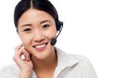 Gullig asiatisk kvinnlig som operatör för hjälpskrivbord Arkivfoto
