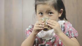 Gullig asiatisk liten flicka som dricker varmt te arkivfilmer