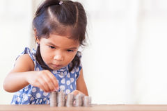 Gullig asiatisk liten flicka som spelar med mynt som gör buntar av pengar Arkivfoto