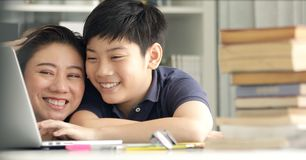 Gullig asiatisk moder som hjälper din son som gör din läxa royaltyfria bilder