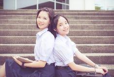 Gullig asiatisk thailändsk hög benägenhet för skolflickastudentpar arkivfoto