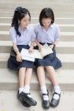 Gullig asiatisk thailändsk hög läsning för skolflickastudentpar arkivbilder