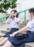 Gullig asiatisk thailändsk hög skolflickastudent i skolalikformig som skrattar med gyckel royaltyfria foton