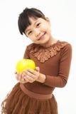 Gullig asiatisk unge med ett äpple Arkivfoto