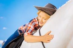 Gullig att bry sig cowboyflicka som kramar hennes favorit- vita häst royaltyfria bilder