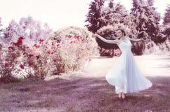 Gullig, attraktiv, försiktig, romantisk sinnlig flicka i en romantisk frisyr som bär en vit klänning Hon dansar i den frodiga trä Royaltyfria Foton