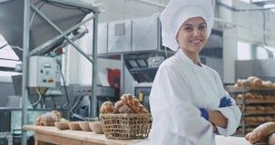 Gullig bagarekvinna framme av kameran som ser rak och ler på stort kommersiellt kök, industriell maskin lager videofilmer