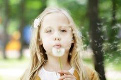 Gullig barnflicka som blåser maskrosen Arkivbilder