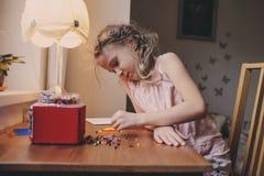Gullig barnflicka som spelar med mosaiken som är hemmastadd i hennes rum Arkivfoton