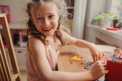 Gullig barnflicka som spelar med mosaiken som är hemmastadd i hennes rum Fotografering för Bildbyråer
