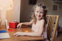 Gullig barnflicka som spelar med mosaiken som är hemmastadd i hennes rum Royaltyfri Bild