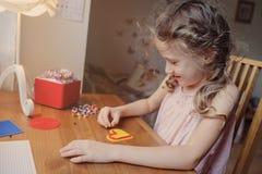 Gullig barnflicka som spelar med mosaiken som är hemmastadd i hennes rum Royaltyfri Foto
