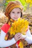 Gullig barnflicka som spelar med stupade sidor arkivbild