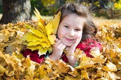 Gullig barnflicka som spelar med stupade sidor i höst royaltyfri foto