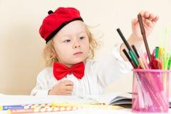 Gullig barnflickateckning med färgrika blyertspennor och tuschpenna i förträning på tabellen Arkivbild