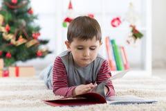Gullig barnpojke som framme läser en bok av julträdet, jultid royaltyfria foton