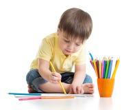 Gullig barnpojketeckning med blyertspennor i förträning Arkivbild