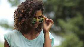 Gullig biracial flickadanandeöga-kontakt, genom att sätta ner solglasögon, medan dansa stock video