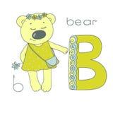 Gullig björn med stängda ögon i gul klänning med ärtor Arkivbilder