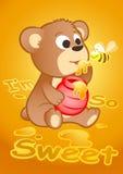 Gullig björn som äter honung med ett bi Arkivfoton