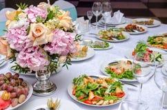 Gullig blommagarnering på tabellen i restorant Arkivfoto